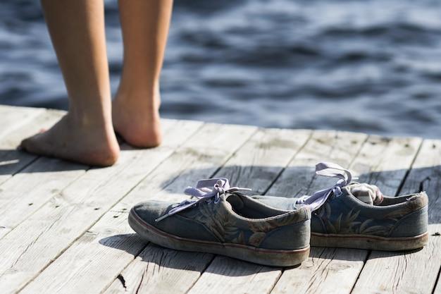 Barfuß person, die nahe schmutzigen schuhen auf einem dock am meer steht