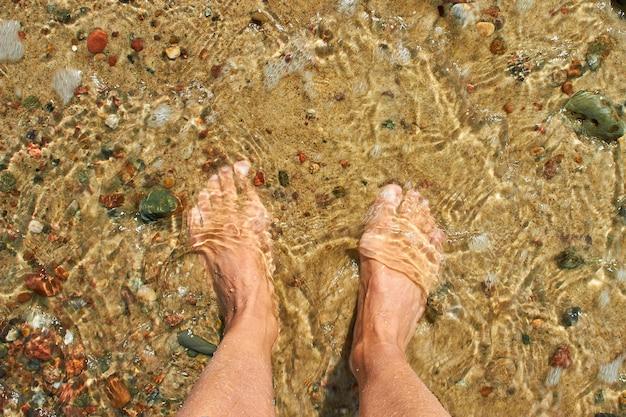 Barfuß weibliche füße auf einem sandstrand mit kieselsteinen, die von einer meereswelle gewaschen werden