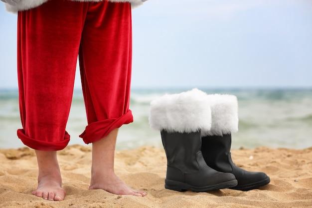 Barfuß weihnachtsmann und stiefel am strand
