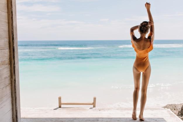 Barfußes mädchen im orangefarbenen badeanzug, das ozean am morgen betrachtet. foto im freien des entspannten weiblichen modells mit gebräunter haut, die meerblick genießt.