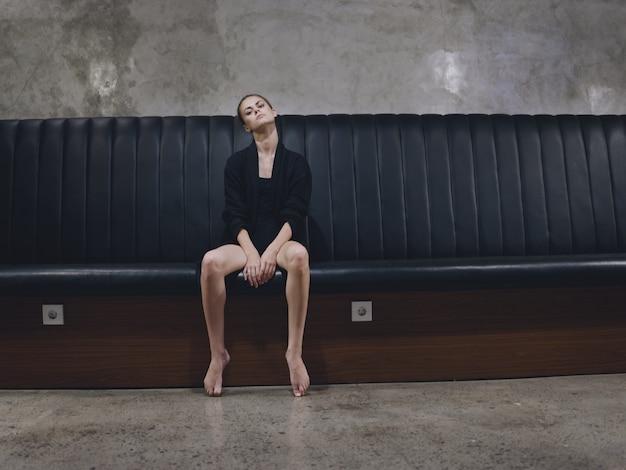 Barfußfrau, die auf einem bankinnenmodell in der dunklen kleidung sitzt