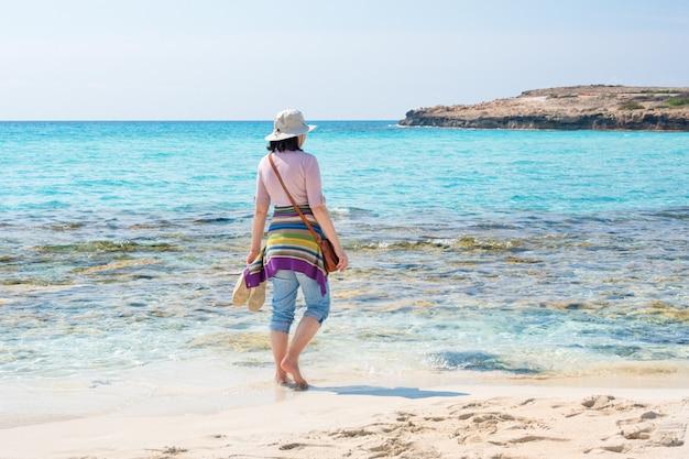 Barfußfrau im hut am strand. sommerferien, urlaub, reisen und personenkonzept