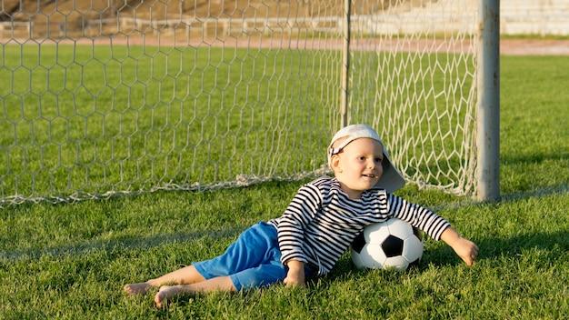 Barfußjunge mit fußball, der auf grünem gras vor torpfosten auf einem sportplatz liegt