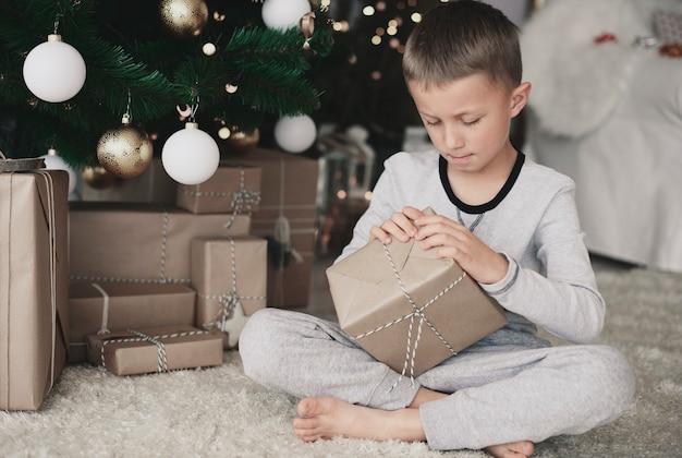 Barfußkind im pyjama, das ein geschenk auf boden öffnet