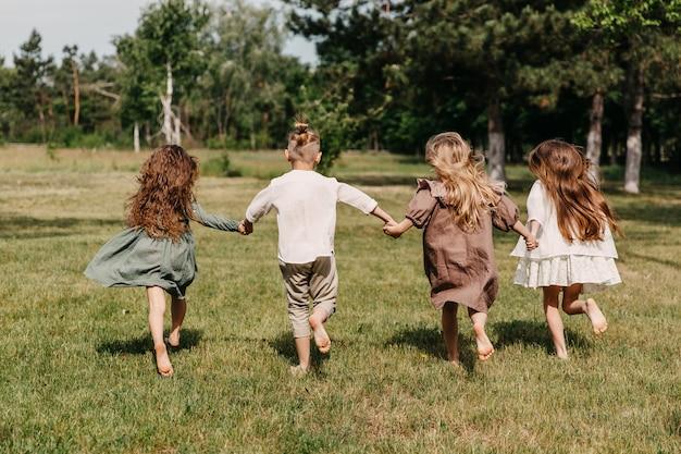 Barfußkinder, die auf einem feld mit grünem gras laufen