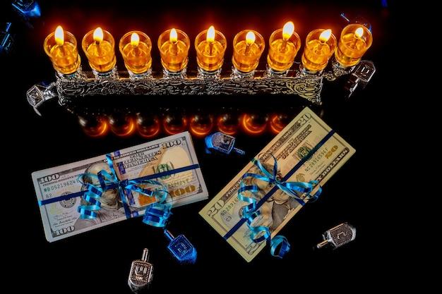 Bargeld als geschenk mit menora für chanukka auf schwarzem hintergrund. jüdische feiertagstradition.