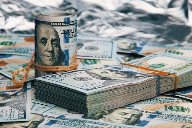 Bargeld hundert dollarscheine, dollarbild. ein stapel und eine rolle von hundert amerikanischen rechnungen.