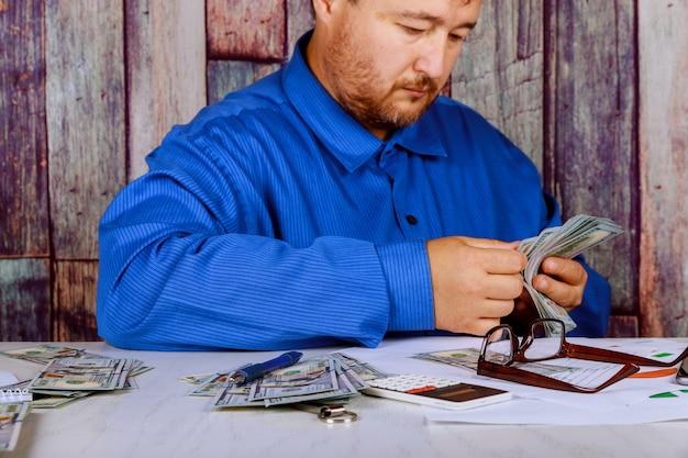Bargeld in den händen mann, der gelddollar in den händen eines mannes zählt, kleidet ein mann im geschäft mit dollar.