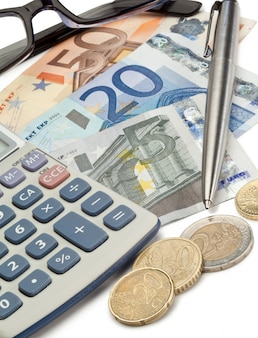 Bargeld, münzen, stift, brille und taschenrechner