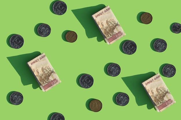 Bargeld und münzen auf einem hellgrünen hintergrund russische rubel-währung muster