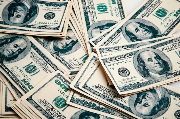 Bargeld von hundert dollarnoten, dollarhintergrund. einhundert us-banknoten sind über den hintergrund verstreut.