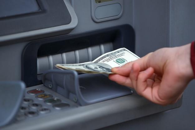Bargeldbezug am geldautomaten, hand mit dollarnoten in der nähe.