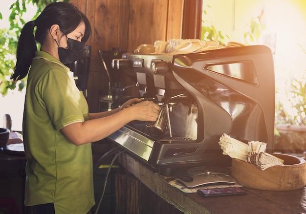 Barista, asiatische frau, die kaffee mit einer kaffeemaschine kocht.