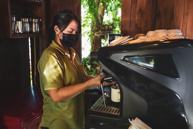 Barista, asiatische frau, die kaffee mit einer kaffeemaschine kocht
