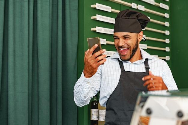 Barista benutzt sein smartphone und lacht, während er im café steht