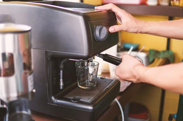 Barista bereitet espresso in seinem café zu