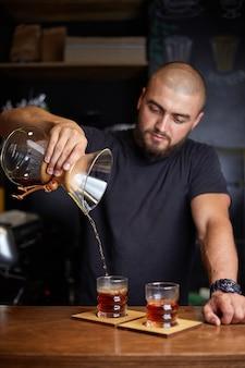 Barista bereitet kaffee mit chemex zu und gießt ihn über die kaffeemaschine