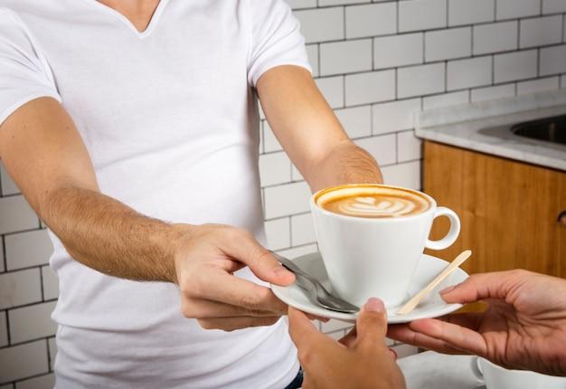 Barista bietet einer person eine tasse kaffee an
