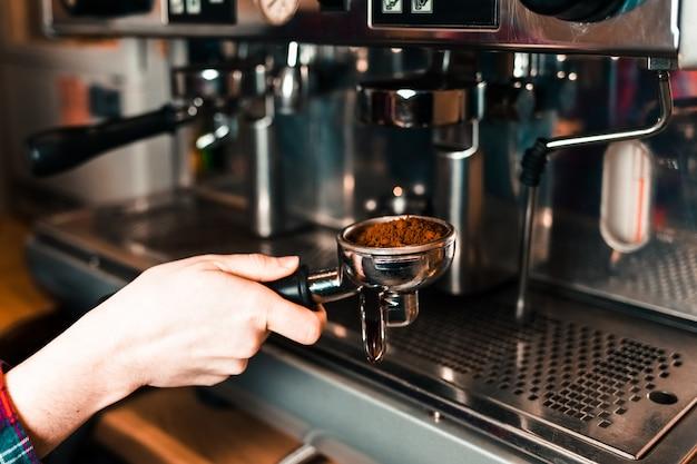 Barista bringt einen halter mit gemahlenem kaffee zu einer kaffeemaschine
