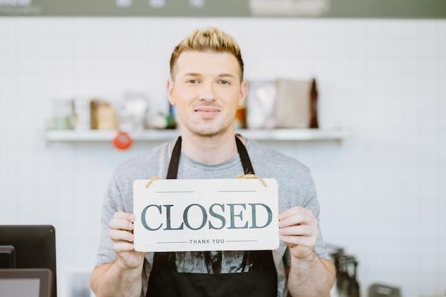 Barista-café-kaffeepersonal hand hält geschäft geschlossenes schild-banner, restaurant geschlossen oder vom covid-19-sperrkonzept wieder geschlossen