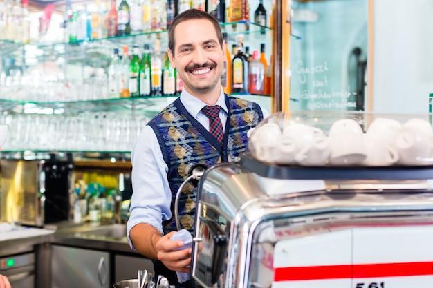 Barista, das kaffee oder espresso in der cafébar zubereitet