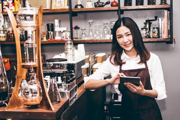 Barista, das tablette in der kaffeestube hält