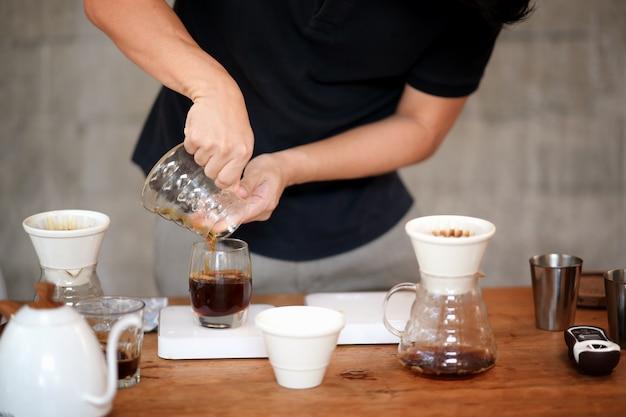 Barista, der auf dem tisch filterkaffee und zubehör herstellt