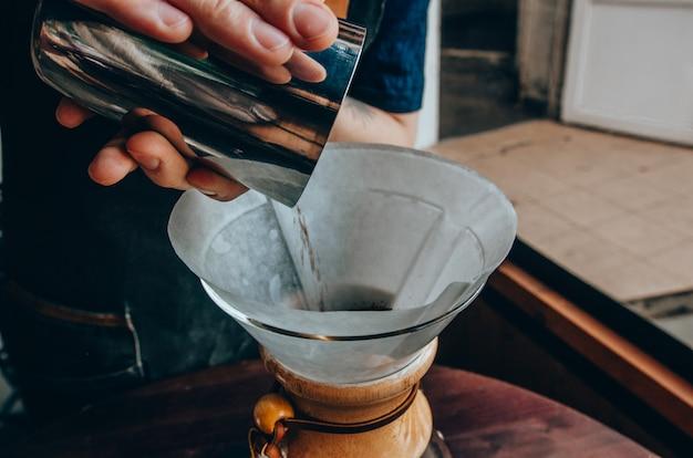 Barista, der den filterkaffee im freien zubereitet