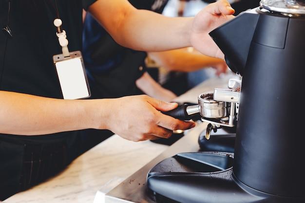 Barista, der den kaffee reibt, der frisch geröstete kaffeebohnen im café reibt.