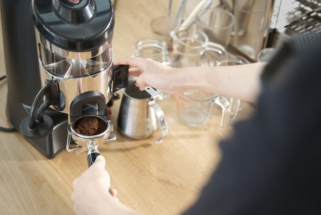 Barista, der hebel der schleifmaschine zieht, um kaffeebohne im kaffeestamp zu bekommen.