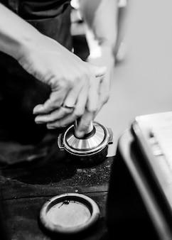 Barista, der in einer kaffeestube, abschluss oben von barista arbeitet, drückt gemahlenen kaffee unter verwendung des stampfers