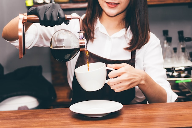 Barista, der kaffee in der kaffeestube hält