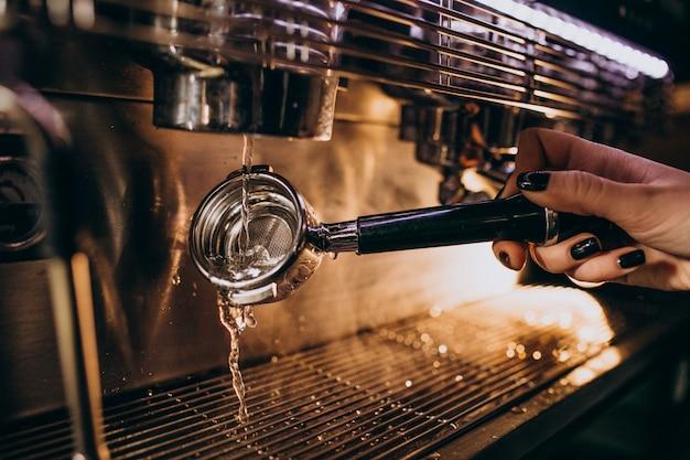 Barista, der kaffee in einer kaffeemaschine zubereitet