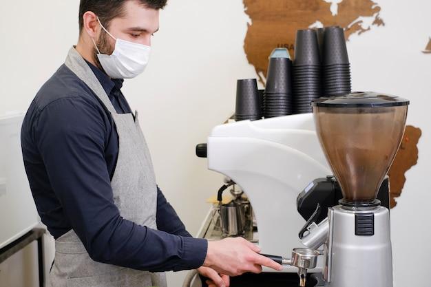Barista, der kaffee in tassen zum mitnehmen im coffeeshop in maske serviert