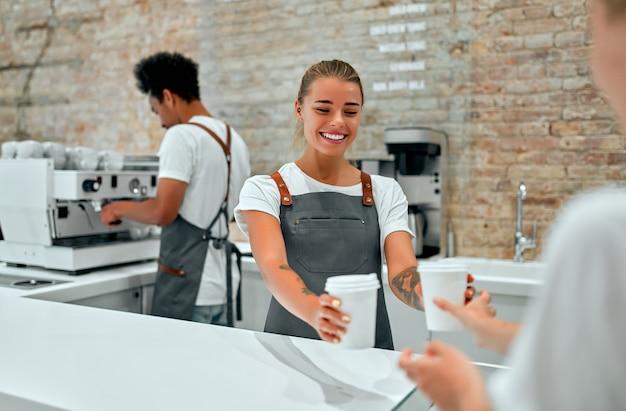 Barista der kaukasischen frau, die dem kunden im café tassen kaffee, latte oder cappuccino gibt.
