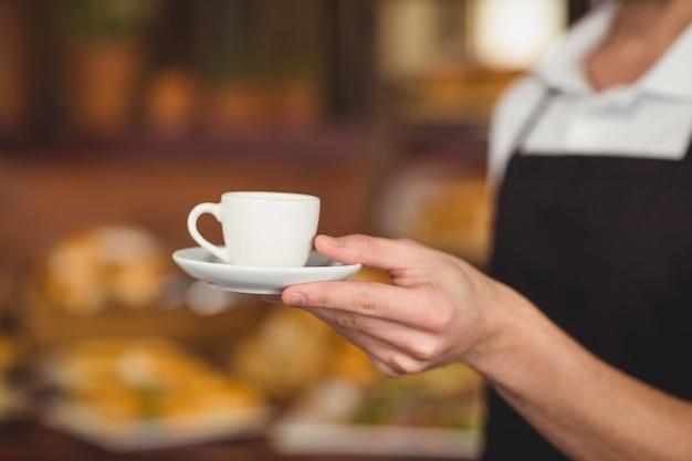 Barista, der tasse kaffee anbietet