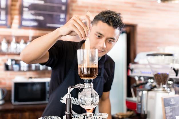 Barista, der tropfenfängerkaffee in der asiatischen kaffeestube zubereitet