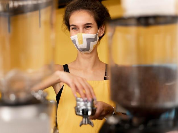 Barista der vorderansicht, die eine gesichtsmaske beim kaffeekochen trägt