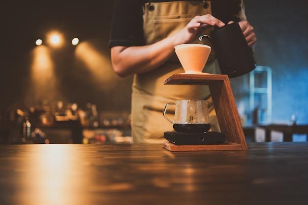Barista, die morgens einen kaffeefilter tropft, getränkegetränk mit frischem schwarzem espresso-aroma, heißes getränk in einer tasse cafés, braunes koffein im barshop-hintergrund