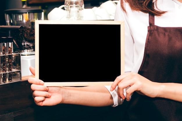 Barista, die tafel im kaffeestubenrestaurant hält