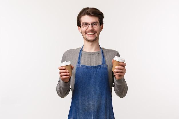 Barista, ein porträt eines unbeschwerten, lächelnden, freundlichen männlichen angestellten in der schürze, machte köstlichen kaffee für die kunden, hielt zwei tassen zum mitnehmen und lachte und lud ein, den besten cappuccino der stadt zu probieren