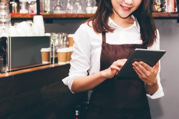 Barista-frau, die digitale tablettenberechnung in der kaffeestube-theke verwendet