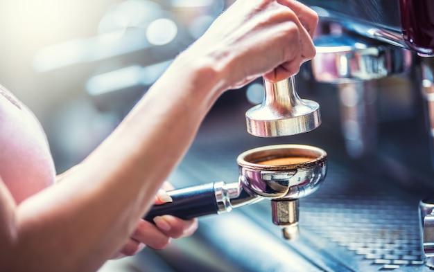 Barista-frau, die einen espresso-kaffee mit portafilter und kaffeestampfer macht.