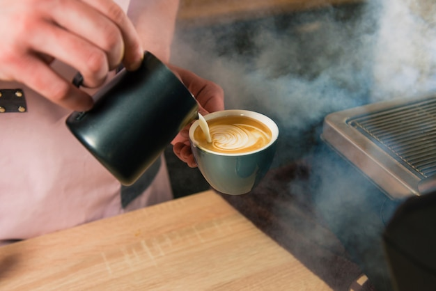 Barista fügt dem espresso auf kunstvolle weise milch hinzu