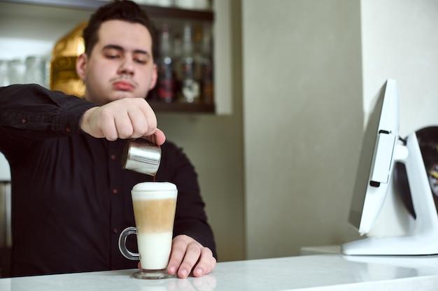 Barista gießt kaffee in ein glas mit einem latte. konzentrieren sie sich auf die zubereitung latte