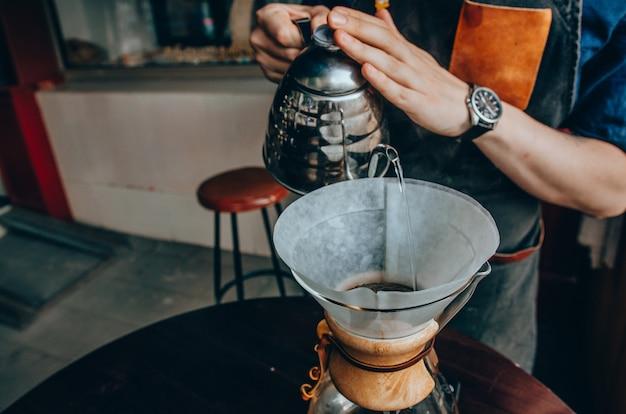 Barista gießt kochendes wasser aus dem kessel
