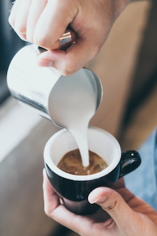 Barista gießt latte art kaffee