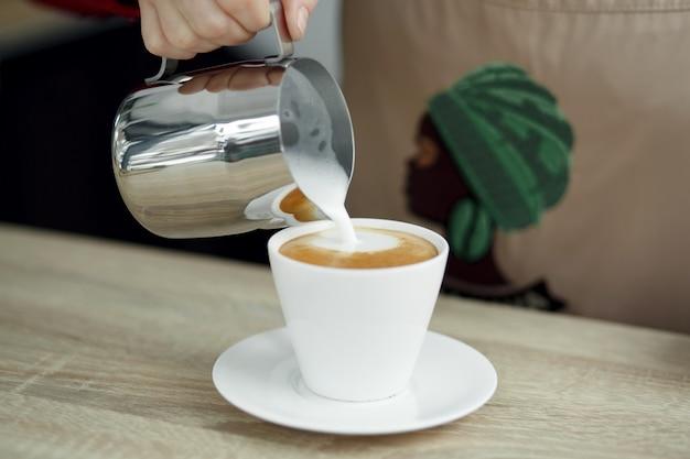 Barista gießt milch aus dem stahltopf in die weiße tasse mit kaffee