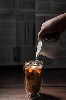 Barista gießt milch in ein glas eiskaffee