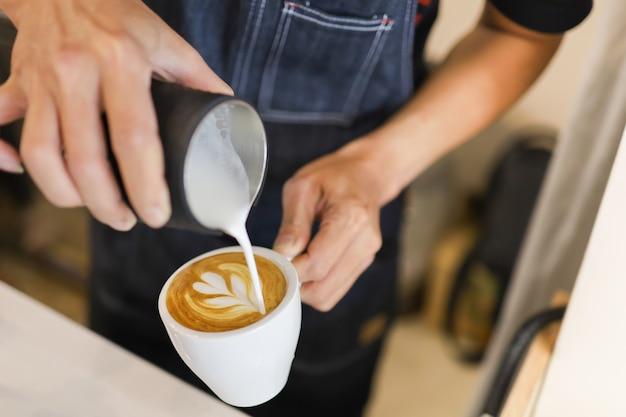 Barista gießt milch in eine weiße tasse heißen kaffee, um latte art zu kreieren.